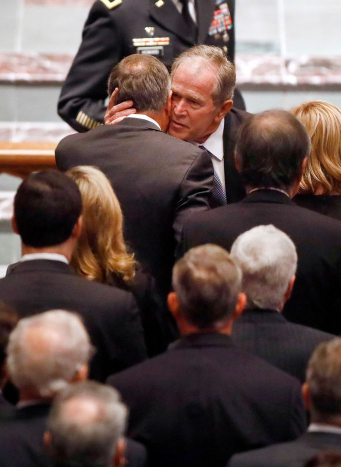 Former President George W. Bush gives a big hug to a friend as he enters the St. Martin's Episcopal Church in Houston for the funeral service of his father.