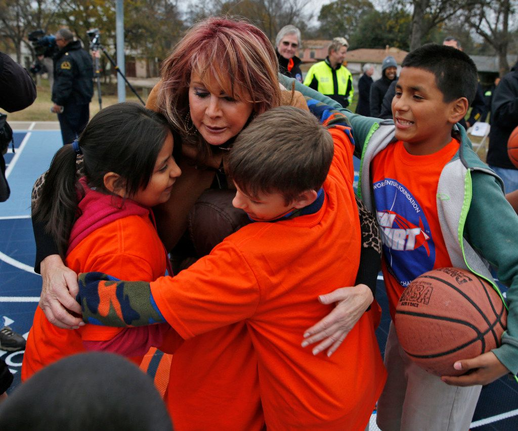 Nancy Lieberman gets hugs from kids during a Dallas Parks and Recreation after-school program on the day of the Dallas Strong Dream Courts dedication ceremony at  Willie Mae Butler Park on Dec. 6.