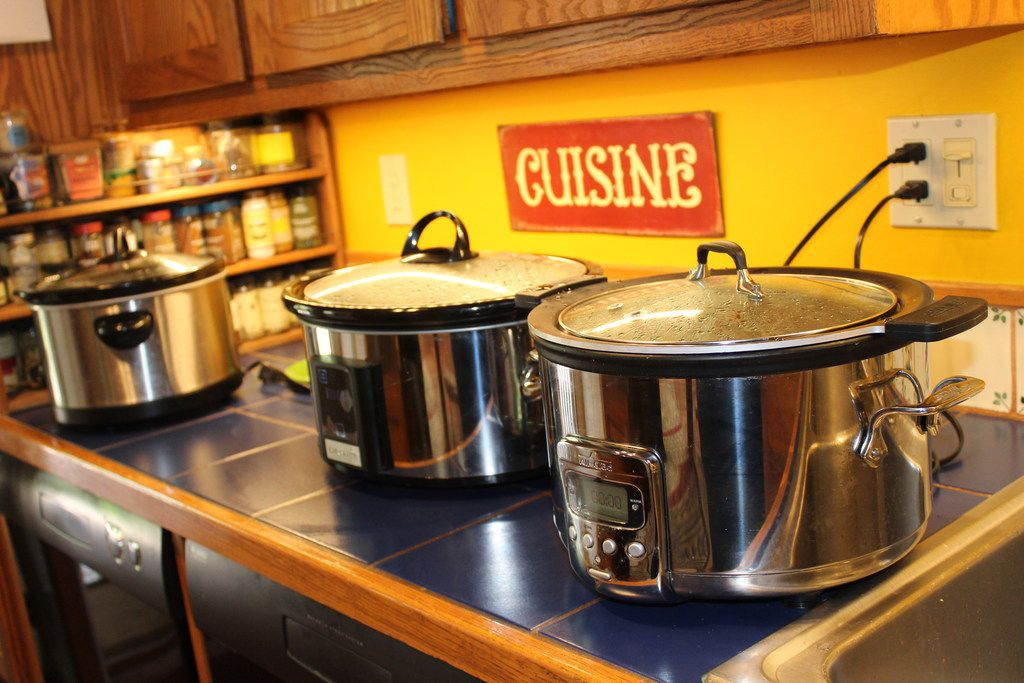 Cheryl Alters Jamison's three slow cookers, lined up and cooking. She borrowed others for testing and evaluation while writing Texas Slow Cooker.