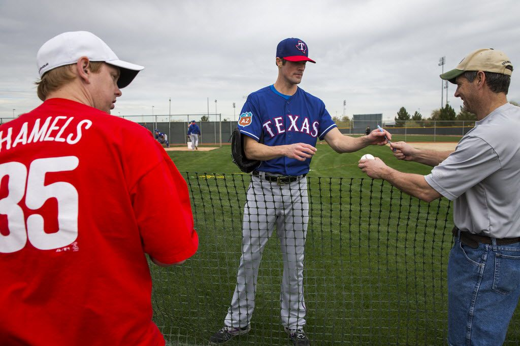 Texas Rangers pitcher Cole Hamels signs autographs for fans during the first full spring training workout for pitchers and catchers at the team's training facility on Friday, Feb. 19, 2016, in Surprise, Ariz.  (Smiley N. Pool/The Dallas Morning News)