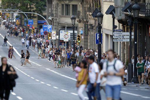 Unas personas caminan por la calle principal de Barcelona, después de que una camioneta van atropelló a varias personas y mató a 13 y dejó a 50 heridas. Foto AP
