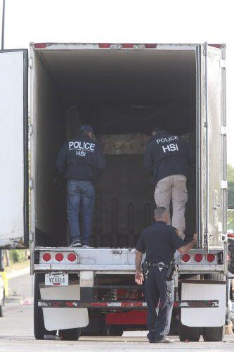 Unos agentes investigan el camión tráiler que iba cargado de indocumentados en el calor de San Antonio. Foto SAN ANTONIO EXPRESS-NEWS
