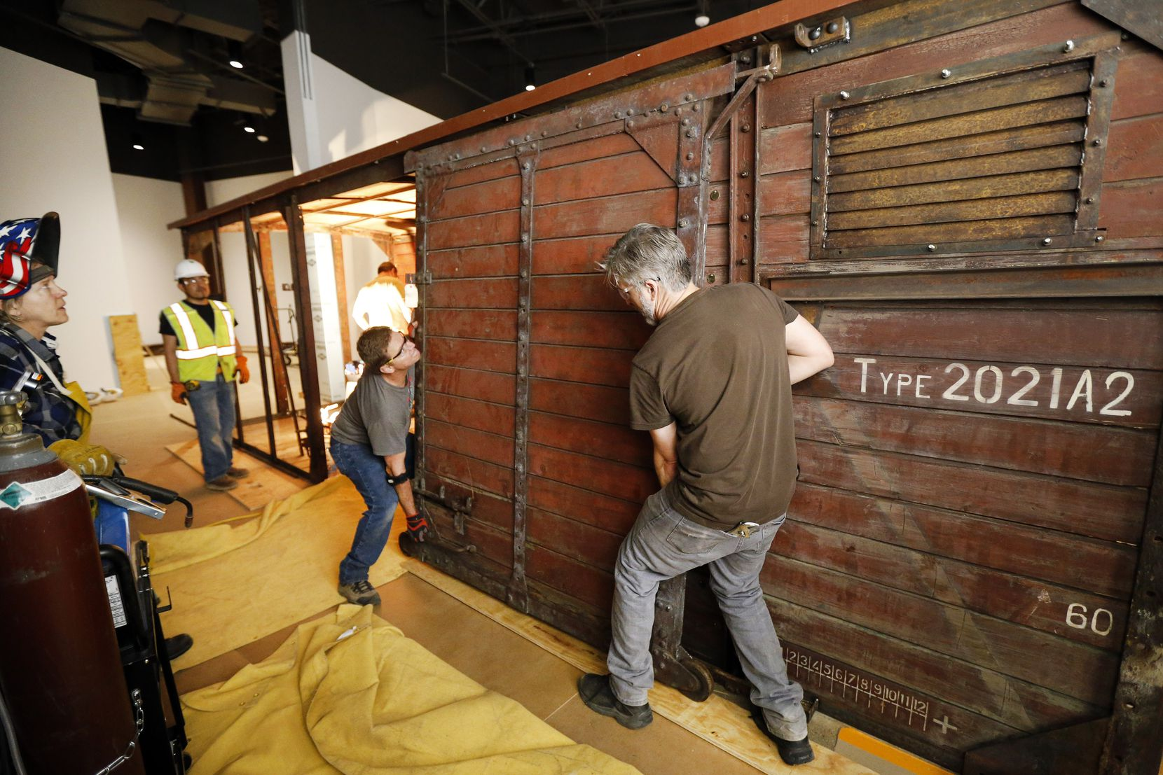 Jeff Green (right) and Dennis Manske erect a door on the rail car that will be on display as part of the new Dallas Holocaust and Human Rights Museum when it opens in September.