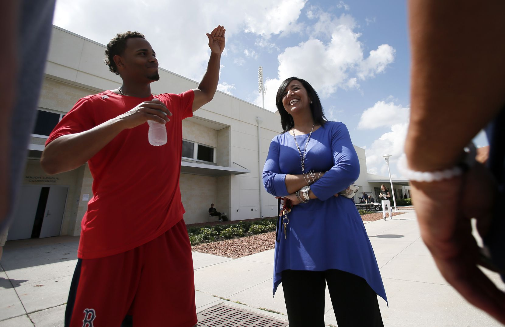 FILE - Boston Red Sox's Xander Bogaerts, left, talks with Raquel Ferreira, Red Sox Vice President of Baseball of Administration before a interleague spring training baseball game against the Miami Marlins in Fort Myers Fla., March 6, 2015.