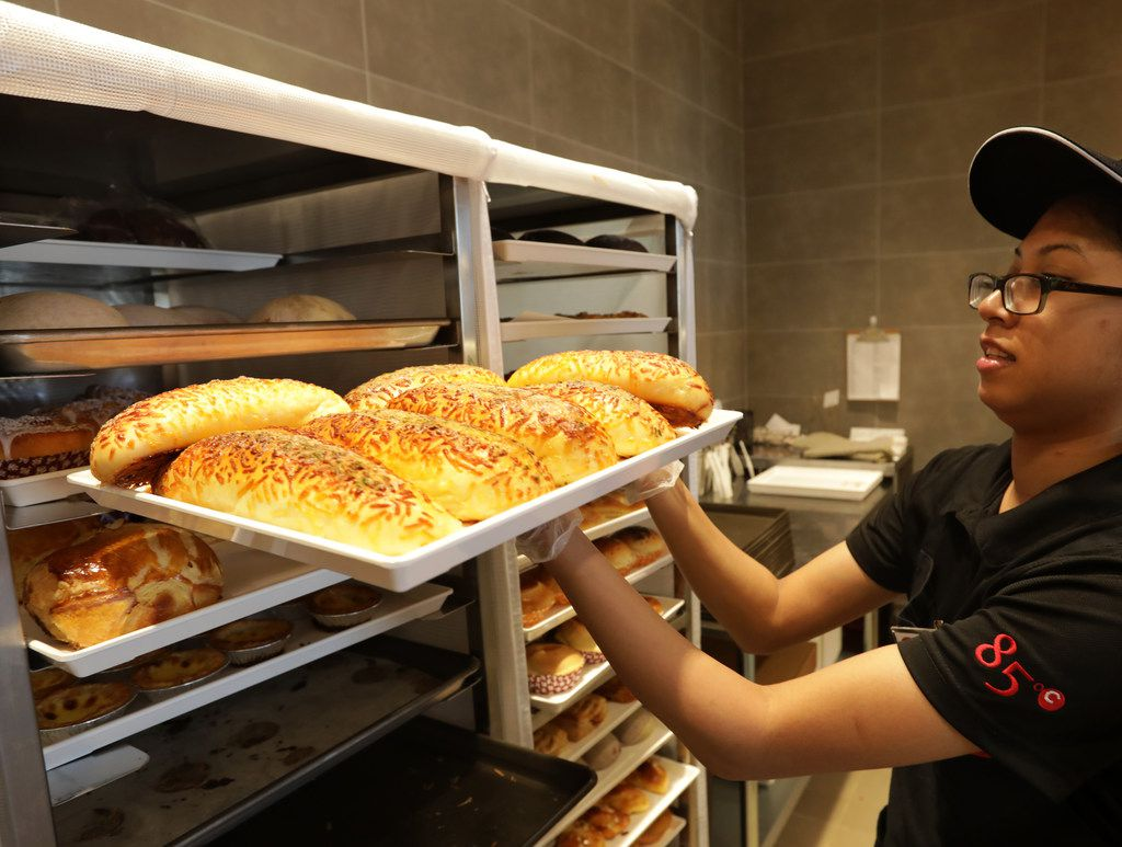 Monica Son prepares to stock the pastry shelves during the opening of 85°C Bakery Cafe in Frisco.