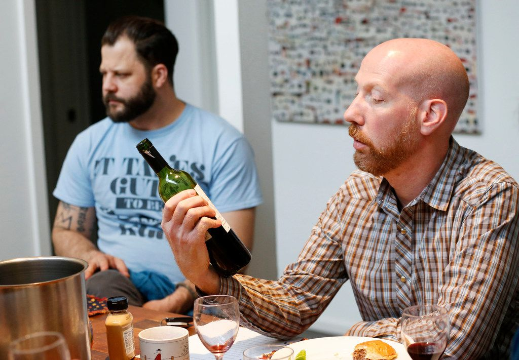 James Tidwell (right) reads the back of a wine bottle during a wine panel tasting with chef Chad Houser.