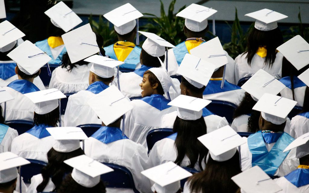 Graduates look for their parents in the audience during the Wilmer-Hutchins High School graduation at Ellis Davis Field House in Dallas on June 2, 2018.