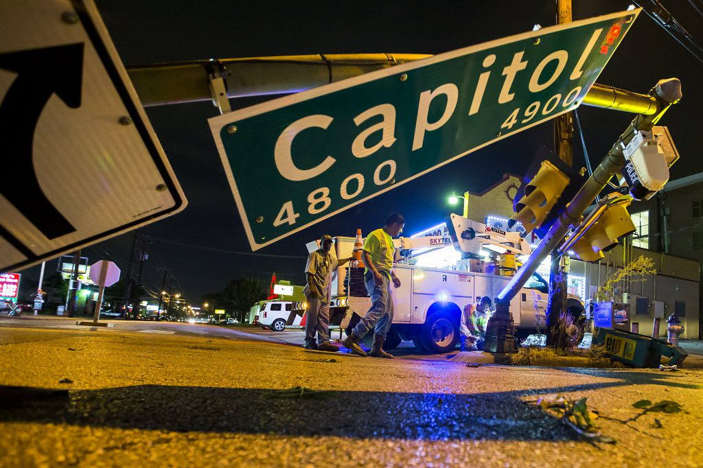 City of Dallas crews work to repair a traffic light that was knocked over into the intersection of Fitzhugh and Capitol after storms tore through the area on June 27, 2016.