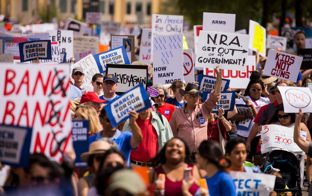 """Demonstrators march down Young Street near Dallas City Hall during a rally and march in support of gun safety laws on March 24, 2018. The """"March For Our Lives"""" event was held in conjunction with hundreds of other marches across the nation in the wake of last month's deadly school shooting in Parkland, Fla., that killed 17 students and staff."""