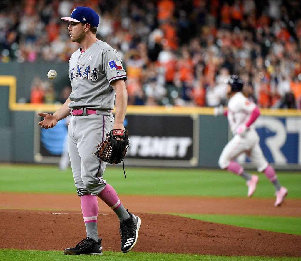 Texas Rangers starting pitcher Adrian Sampson, left, walks away from the mound as Houston Astros' George Springer, back right, rounds the bases after hitting a solo home run during the first inning of a baseball game, Sunday, May 12, 2019, in Houston. (AP Photo/Eric Christian Smith)