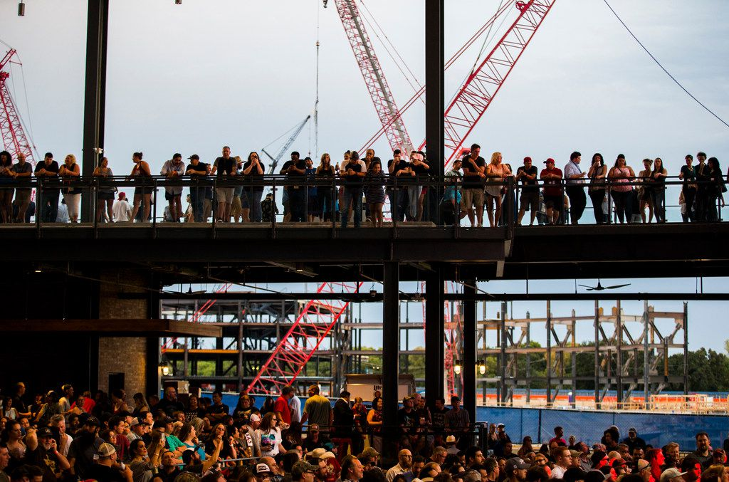 Guests watch Eleven Hundred Springs from the balcony of the Arlington Backyard venue during the grand opening celebration for Texas Live.