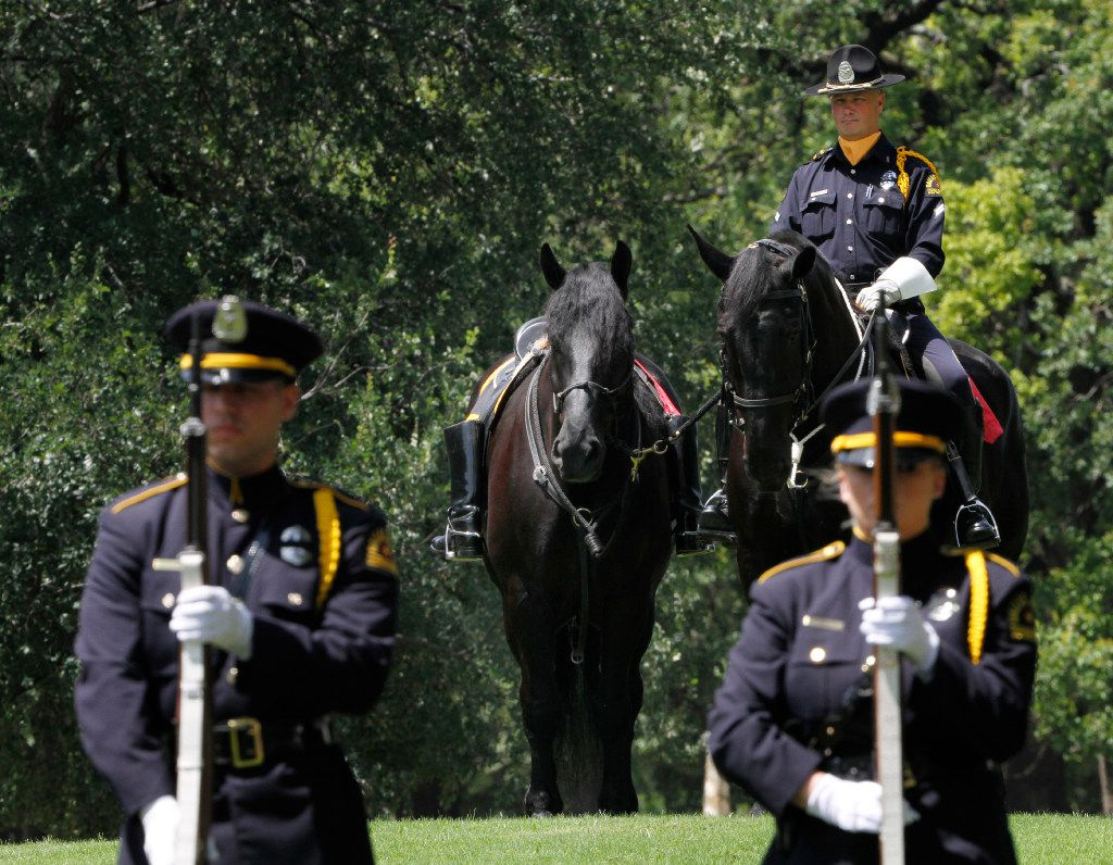 Dallas Police officer Ron Cunningham sits with a riderless horse as 21 Gun Salute officers file in formation during Wednesday's memorial service for fallen peace officers. (David Woo/The Dallas Morning News)