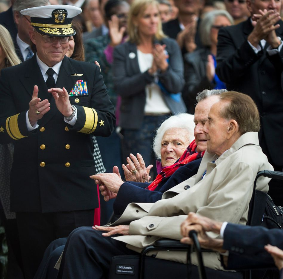 Adm. Chip Miller, former commanding officer of the USS George H.W. Bush (CVN 77), and Barbara Bush applaud former President George H. W. Bush and former Sen. Bob Dole during a Pearl Harbor 75th Anniversary commemoration at the George Bush Presidential Library on Wednesday, Dec. 7, 2016, in College Station, Texas. (Smiley N. Pool/The Dallas Morning News)