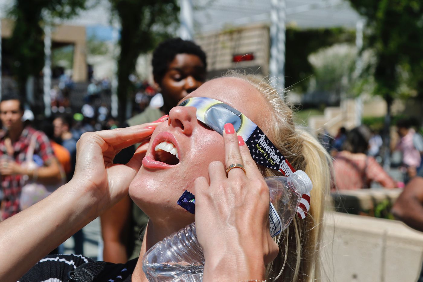 University of Texas at Dallas student Ashton Murray reacts as she views the solar eclipse through borrowed eclipse glasses. She was one of hundreds of students and faculty who stopped by the McDermott Library eclipse party.