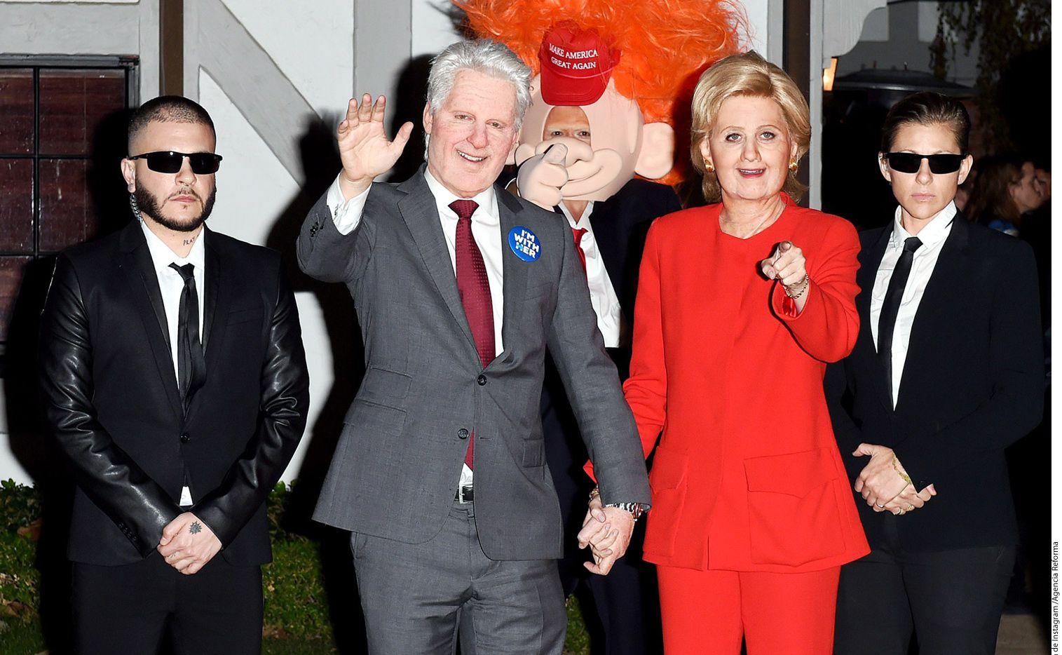 Katy Perry (de rojo) y Orlando Bloom (atrás con peluca roja) se disfrazaron como Hillary Clinton y Donald Trump./AGENCIA REFORMA