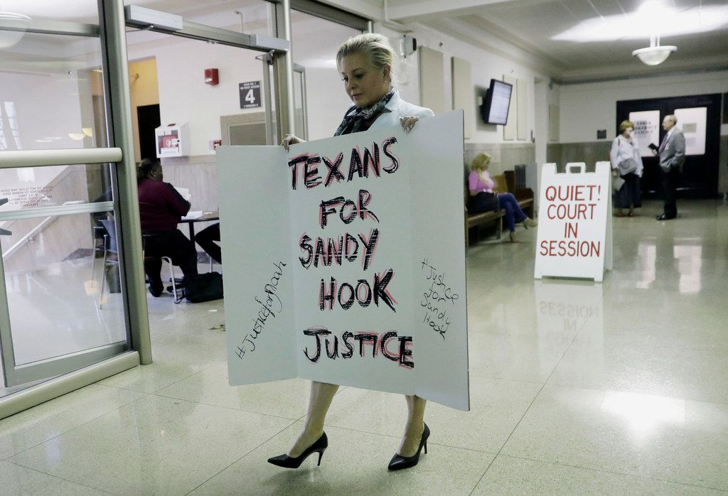 Kelly Jones, ex-wife of Infowars host Alex Jones, carries a sign as she arrives at the Travis County Courthouse, Wednesday, Aug. 1, 2018, in Austin.  Alex Jones wants a Texas judge to dismiss a defamation lawsuit filed against him by families of some of the children killed in the 2012 mass shooting at Sandy Hook Elementary School in Connecticut.