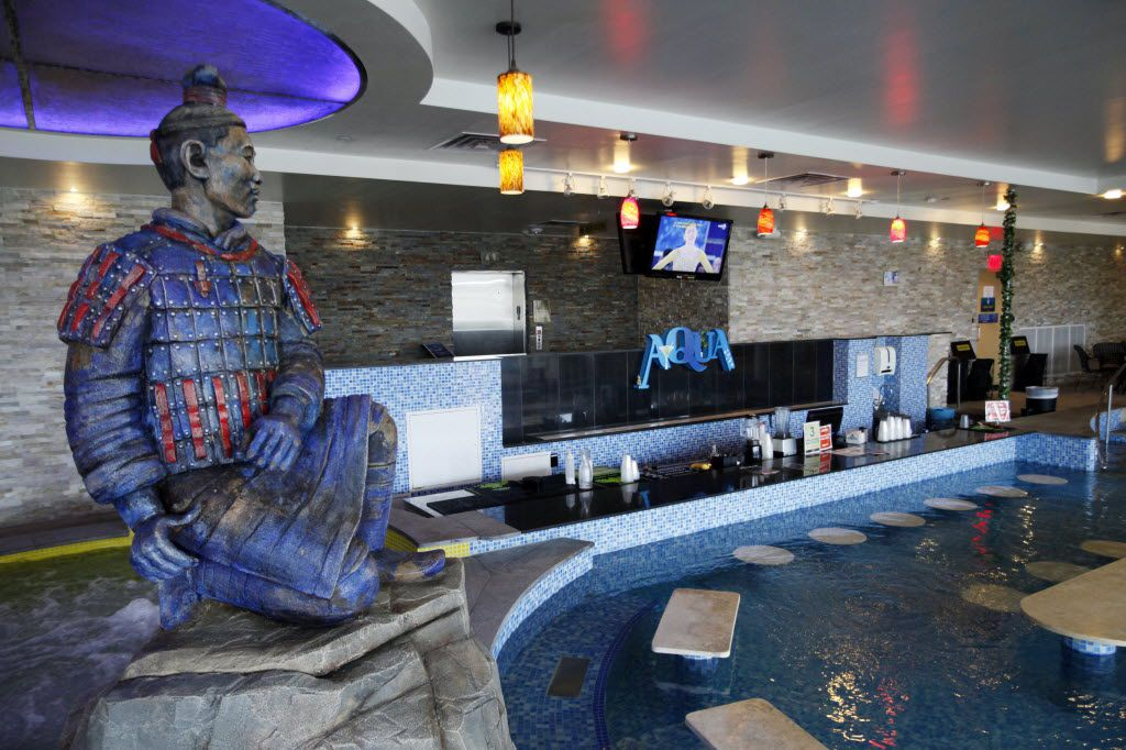 A Japanese statue decorates the shallow pool area of the Aqua bar inside Spa Castle hotel and resort, on Wednesday, Feb. 19, 2014 in Carrollton.