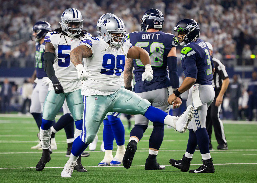 FILE - Cowboys defensive tackle Antwaun Woods (99) celebrates a sack of Seahawks quarterback Russell Wilson (3) during the first half of an NFC wild-card game at AT&T Stadium on Saturday, Jan. 5, 2019, in Arlington.