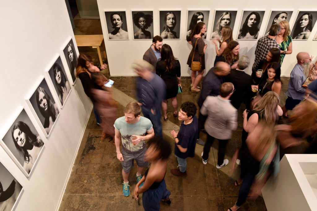 People are blurred with a slow camera shutter as they mingle during opening night of Fredrik Broden's exhibit at Tractorbeam's gallery in downtown Dallas.
