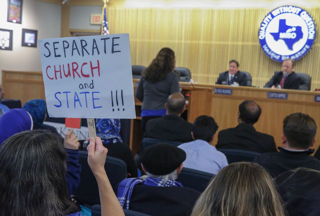 Kristy Fuxa held a separate church and state sign while Amy Bennett spoke at the McKinney ISD board meeting on Jan. 23.