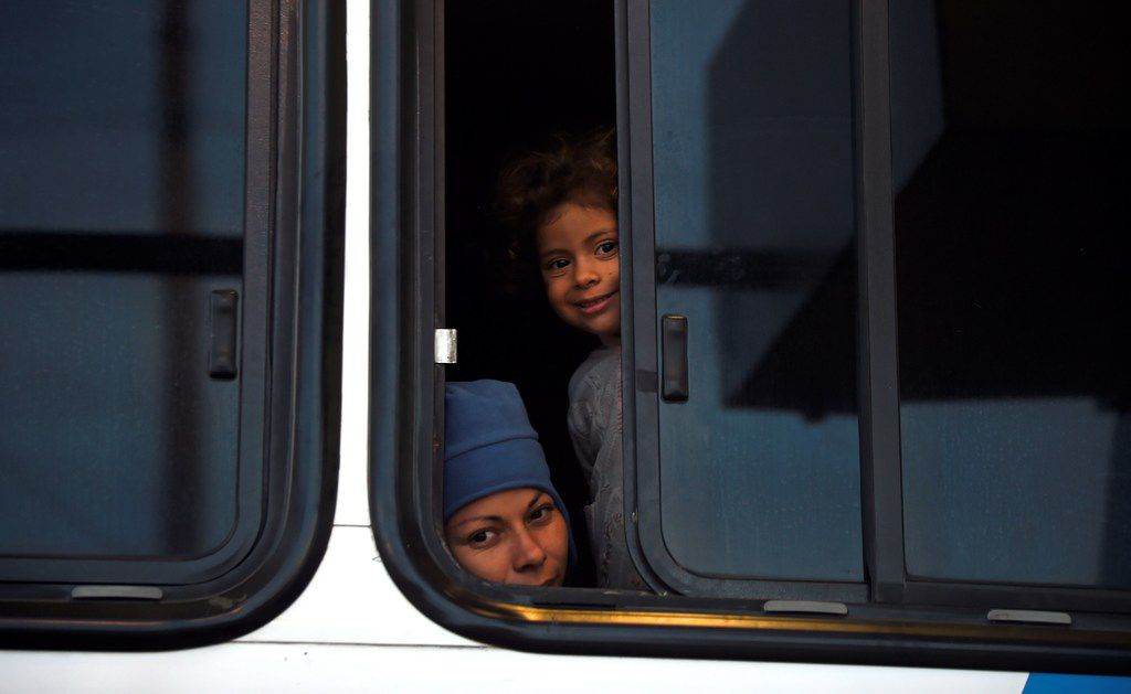 Central American migrants moving in a caravan towards the United States look out from a bus window in Altar, Sonora state, Mexico, on Nov. 14, 2018.
