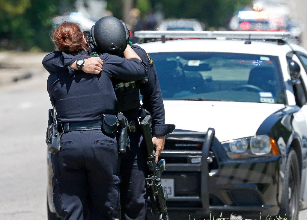 Two Dallas Police Officers comfort each other on the active shooting scene where a Dallas Fire-Rescue paramedic has been shot on Dolphin Road in Dallas, Monday, May 1, 2017.