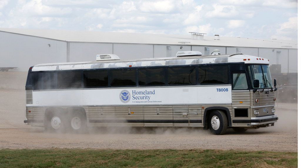 A Homeland Security bus carries detained employees away after the raid at  Load Trail.
