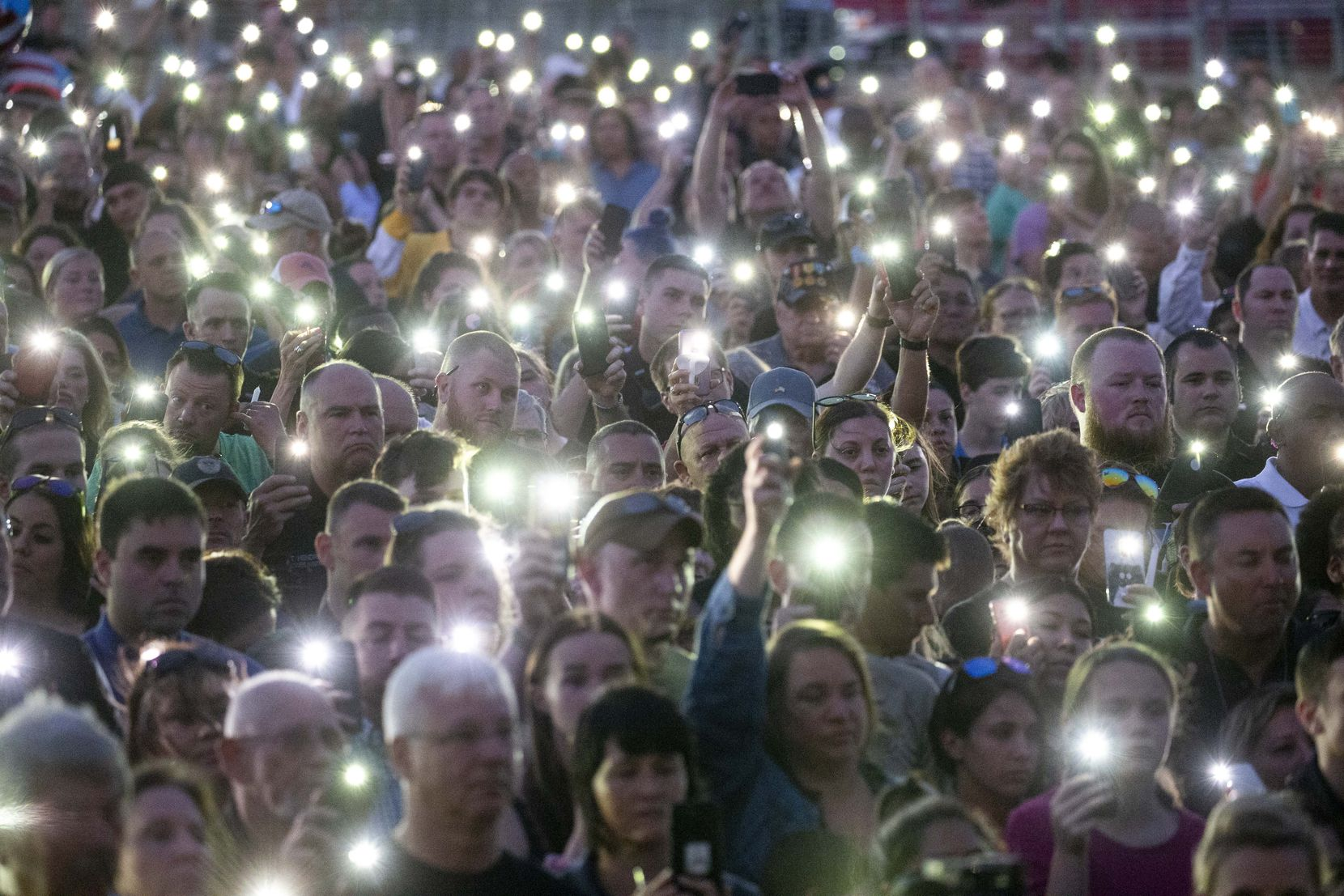 """Cellphone flashlights stood in for candles due to high winds at a vigil Sunday in honor of Grand Prairie police Officer Albert """"A.J."""" Castaneda. Castaneda suffered a fatal fall Friday when a vehicle struck his parked police SUV on a Bush Turnpike overpass, where he was standing outside the vehicle running radar."""