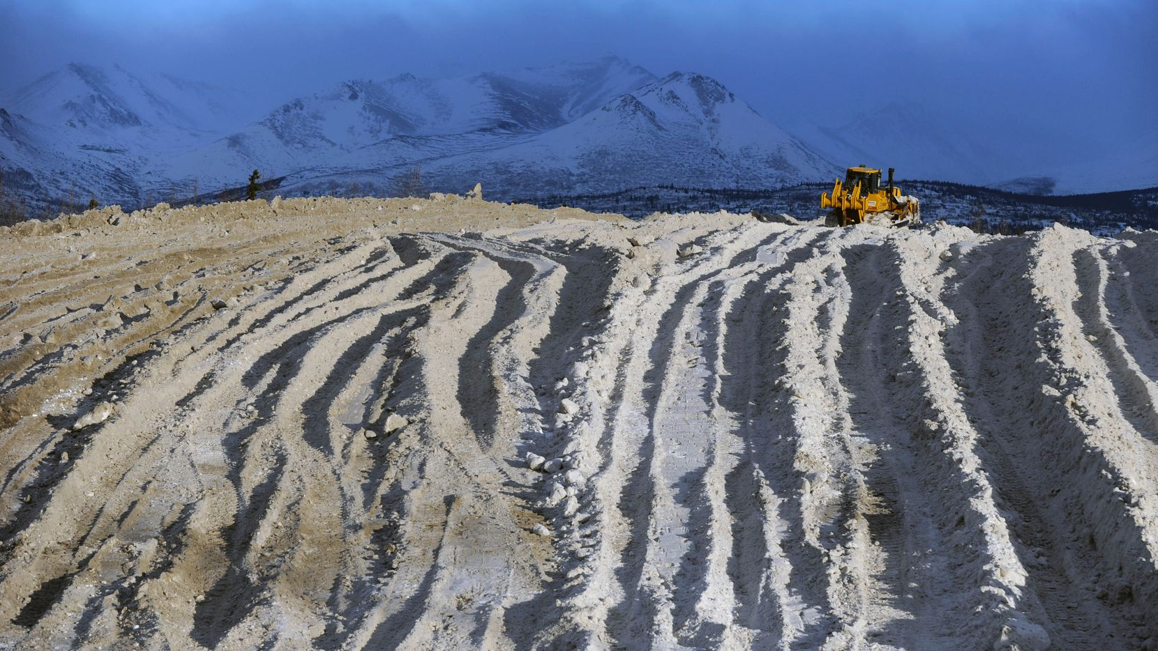 Heavy equipment pushes snow at an Alaska snow dump site in Anchorage.