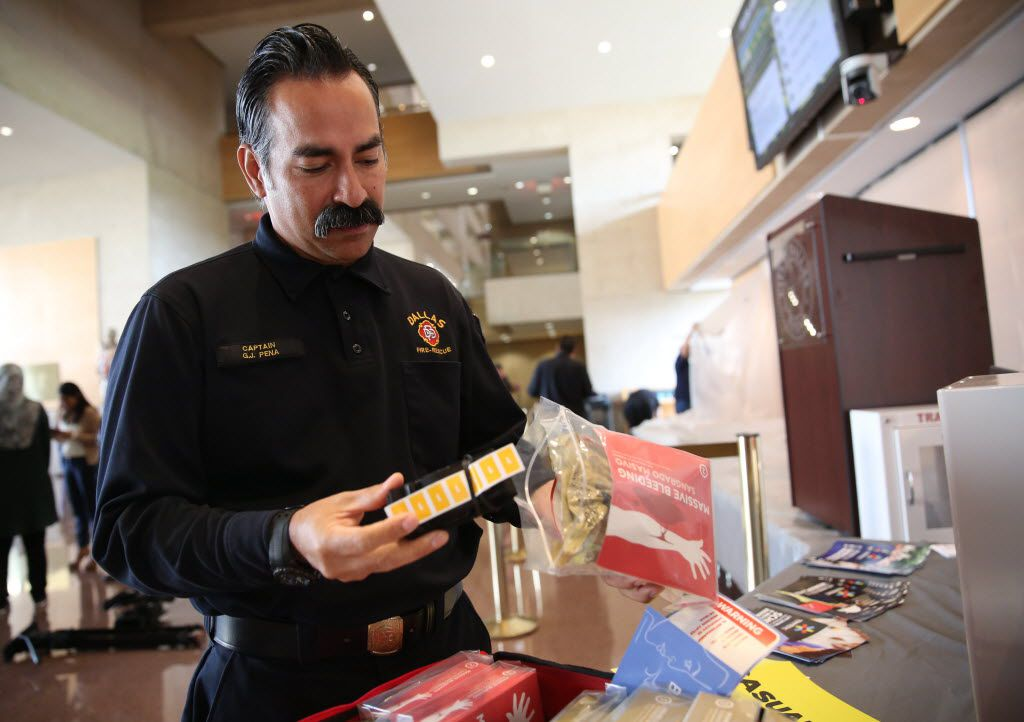 Dallas fire Capt. Gil Pena looks at a trauma kit after a news conference announcing the details of a citywide trauma kit project at Dallas City Hall on Tuesday. (Rose Baca/Staff Photographer)