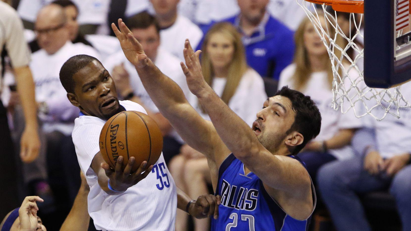 Kevin Durant de Oklahoma trata de lanzar el balón a la canasta ante la marca de Zaza Pachulia de Dallas.