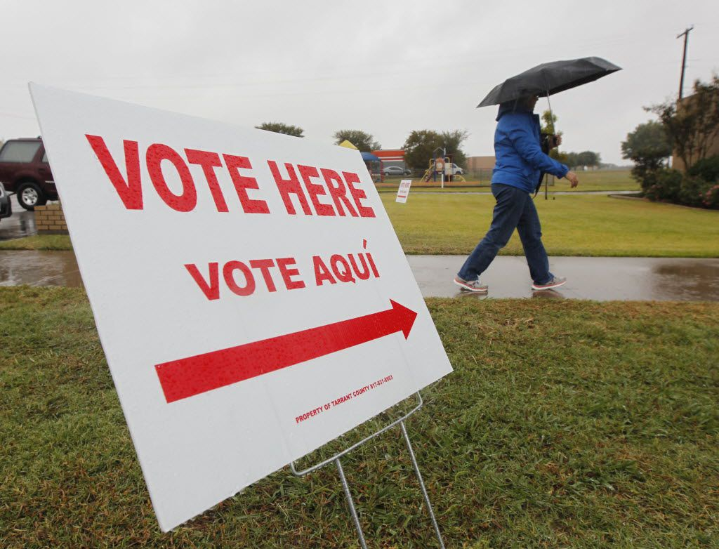 A voter uses an umbrella as she enters the polling place to vote at the United Memorial Christian Church, in Euless, Texas, on Nov. 4, 2014.  (Michael Ainsworth/The Dallas Morning News)