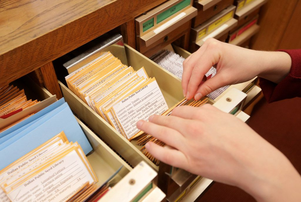 Catherine Gilman thumbs through the seed library, which is housed in old card catalog drawers.