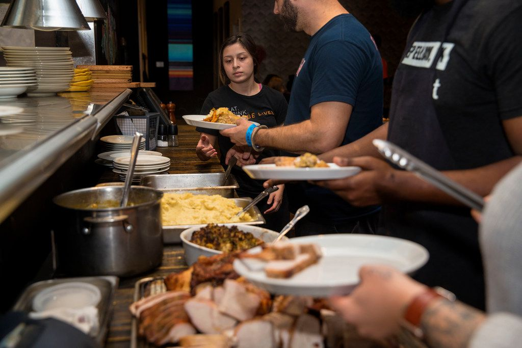 Employee Noemi, 17, grabs a dish from founder Chad Houser during an employee Thanksgiving dinner at Cafe Momentum.