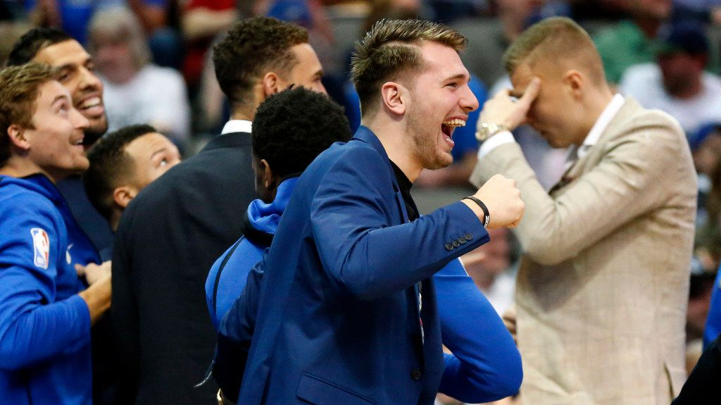 Dallas Mavericks forward Luka Doncic (center) and his teammates react after Dirk Nowitzki threw down a dunk on the opening possession against the Memphis Grizzlies at the American Airlines Center in Dallas, Friday, April 5, 2019. (Tom Fox/The Dallas Morning News)