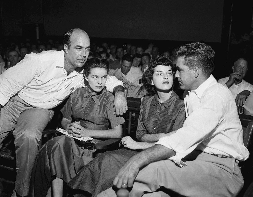 """In this Sept. 23, 1955, file photo, J.W. Milam (left), his wife (second left), Roy Bryant (far right) and his wife, Carolyn Bryant, sit together in a courtroom in Sumner, Miss. Bryant and his half-brother Milam were charged with murder but acquitted in the kidnap-torture slaying of 14-year-old black teen Emmett Till in 1955 after he allegedly whistled at Carolyn Bryant. The men later confessed in a magazine interview but weren't retried; both are now dead. Citing """"new information,"""" the U.S. Justice Department has reopened the investigation into Till's death. (AP Photo, File)"""