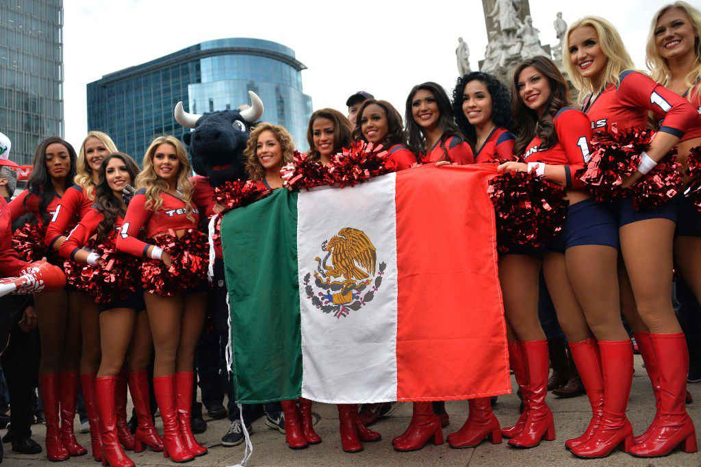 Houston Texans leader pose with a Mexican flag in Mexico City. As the NFL returns to Mexico with a regular season game on Monday night, passion for the sport is soaring in this country where the round-ball game of football has long been king. (Pedro Pardo/Agence France-Presse)