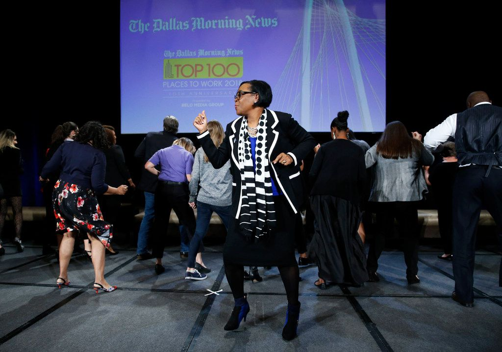 Dallas Mavericks CEO Cynthia Marshall dances with people from the luncheon during her presentation at the Top 100 luncheon at the Omni hotel in Dallas on Thursday, November 1, 2018.