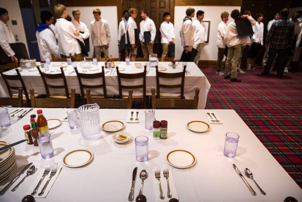 Students, who serve as waiters for meals, set the dining hall tables at Woodberry Forest School.