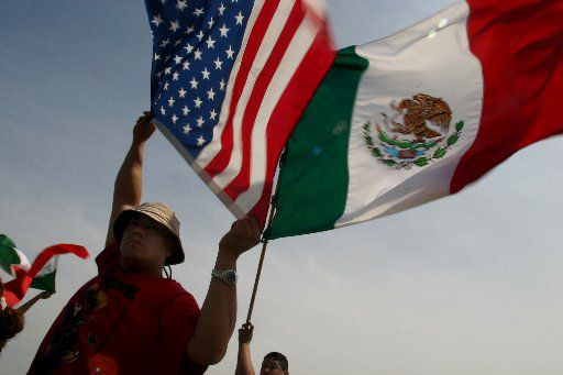 Eduardo Marquez (left) and Jaime Rosas, 14, wave the American and Mexican flag during a protest at Kiest Park in Dallas on March 28, 2006.