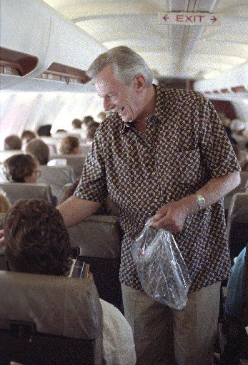 Southwest Airlines chief Herb Kelleher passes out peanuts to customers on a flight from Dallas to San Antonio.