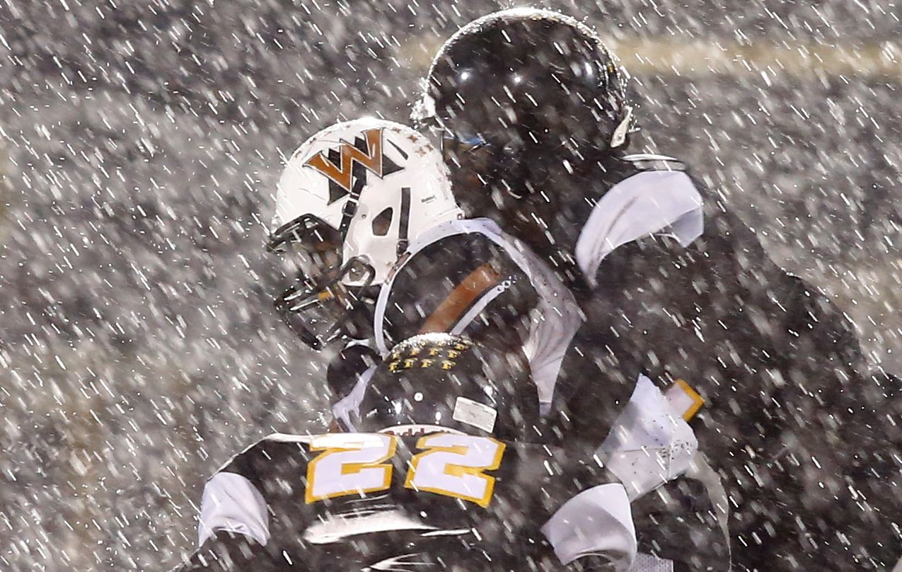 Rain pours down as West Mesquite's Curtis Williams (6) tries to break away from Forney's Donovan Graham (22) in the first half of their high school football game in Forney, Texas, Friday, October 30, 2015.