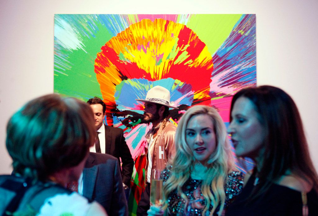 "Hair designer Charlie Price, in a hat, is photographed in front of a painting of George Michael during the MTV RE:DEFINE gala at the Dallas Contemporary on Friday evening in Dallas. The painting, by Damien Hirst, is titled, ""Beautiful Beautiful George Michael Love Painting."" (Ben Torres/Special Contributor)"