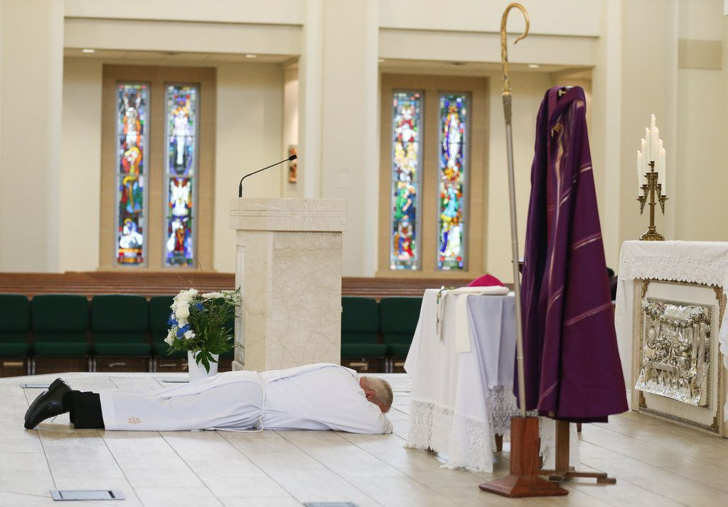 Bishop Edward J. Burns prostrates on the altar as a sign of humility and penance during a Ceremony of Sorrow on Oct. 9, 2018, at St. Cecilia Catholic Church in Dallas. After the service, the first of four town halls was held to address the crisis of sexual abuse by clergy, including allegations of abuse by the former pastor of St. Cecilia Catholic Church, the Rev. Edmundo Paredes.