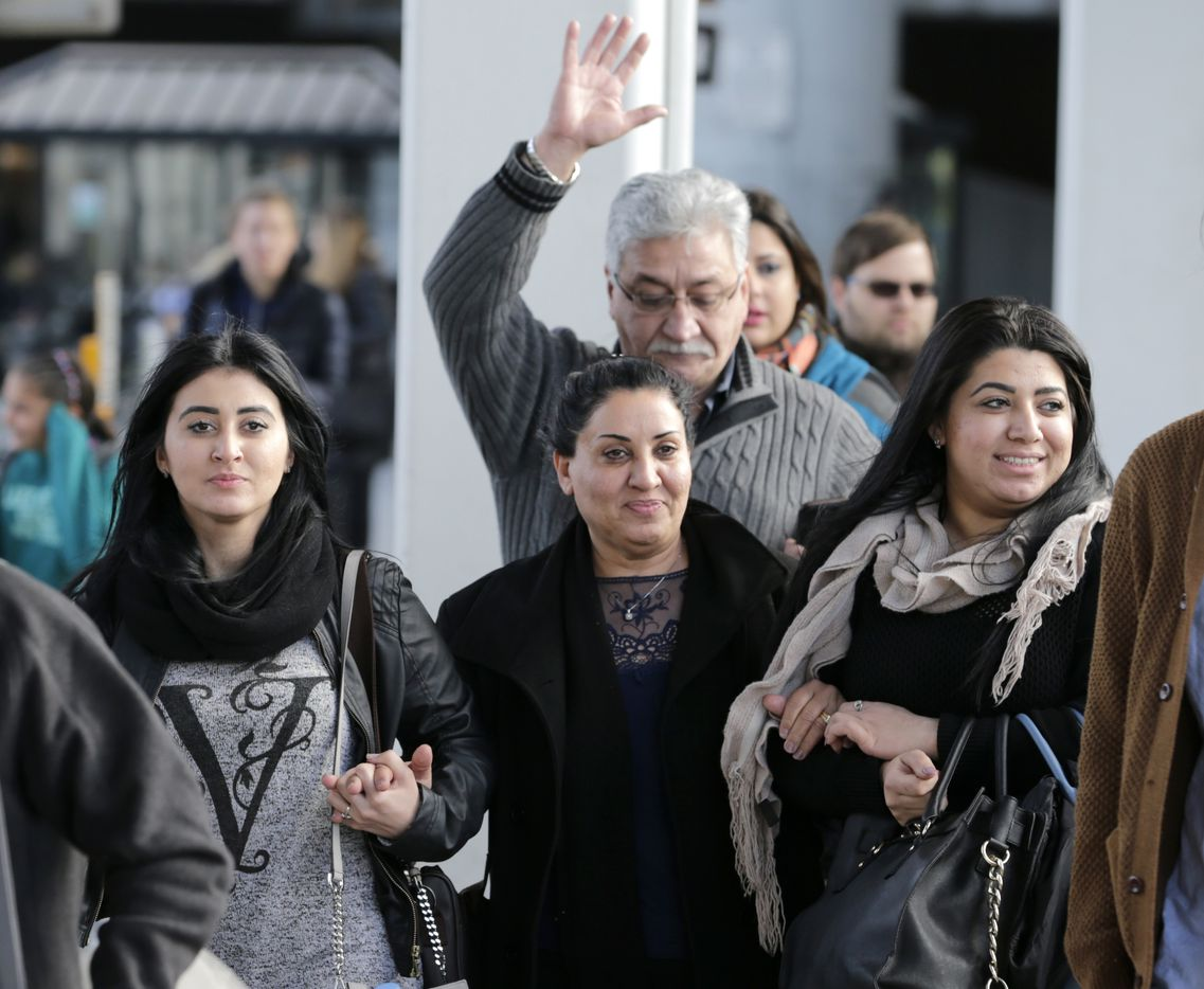 Iman Alknfushe, center, exits John F. Kennedy International airport with her daughters Elaf, right, and Anfal Hussain in New York, Sunday, Jan. 29, 2017. Attorneys advocating on her behalf said Alknfushe was coming from Iraq and had been detained at the airport for more than 30 hours.