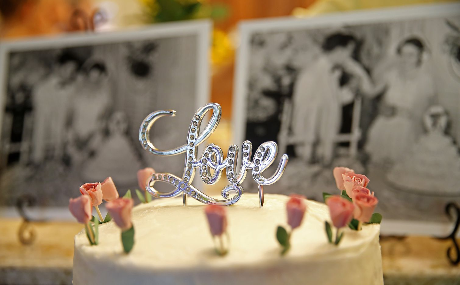 A cake sits on the table in front of the pictures of Frank and Carole Barbosa at their 65th wedding anniversary celebration at their daughter Ani Stone's home in Dallas, Wednesday, July 26, 2017.