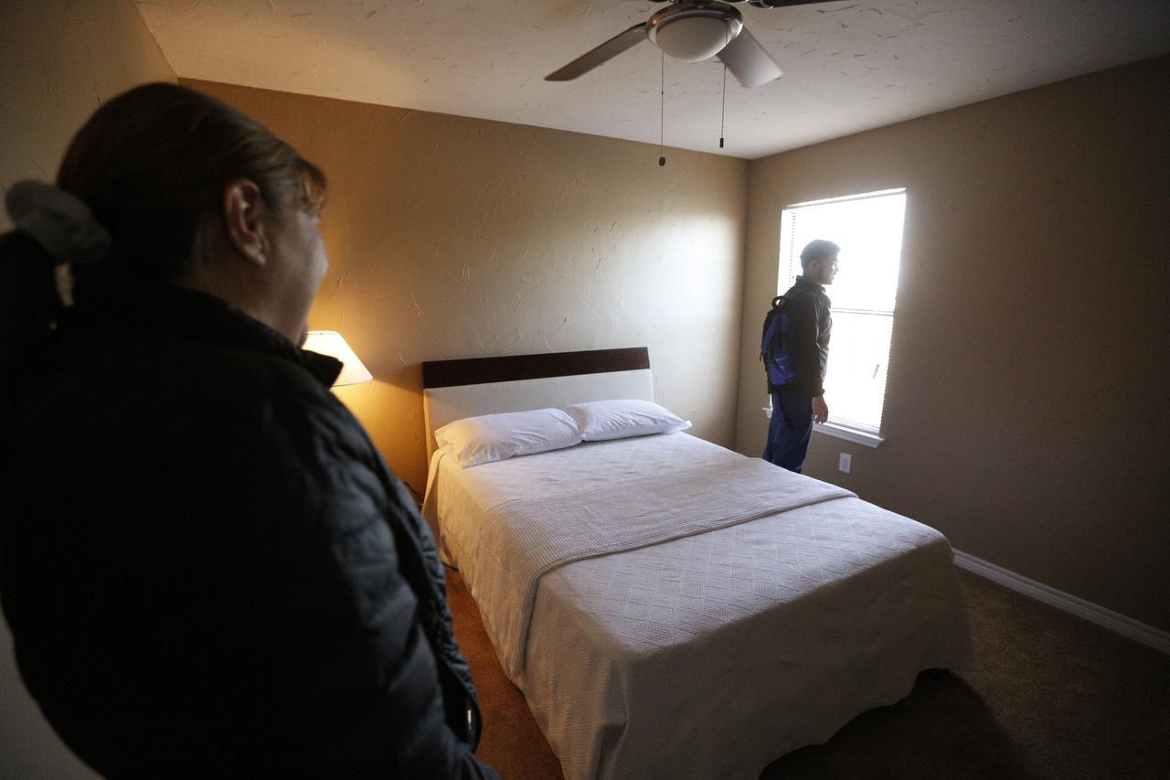 Martha Salazar observa a su hijo Pedro mientras contempla la vista desde una ventana en su nueva casa temporal. La vivienda de los Salazar en Garland fue destruida por un tornado a finales de diciembre. (DMN/NATHAN HUNSINGER)
