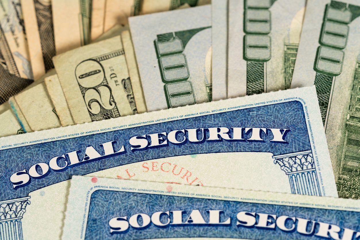 Tarjetas del Seguro Social encima de varios billetes de dolar. iStock.