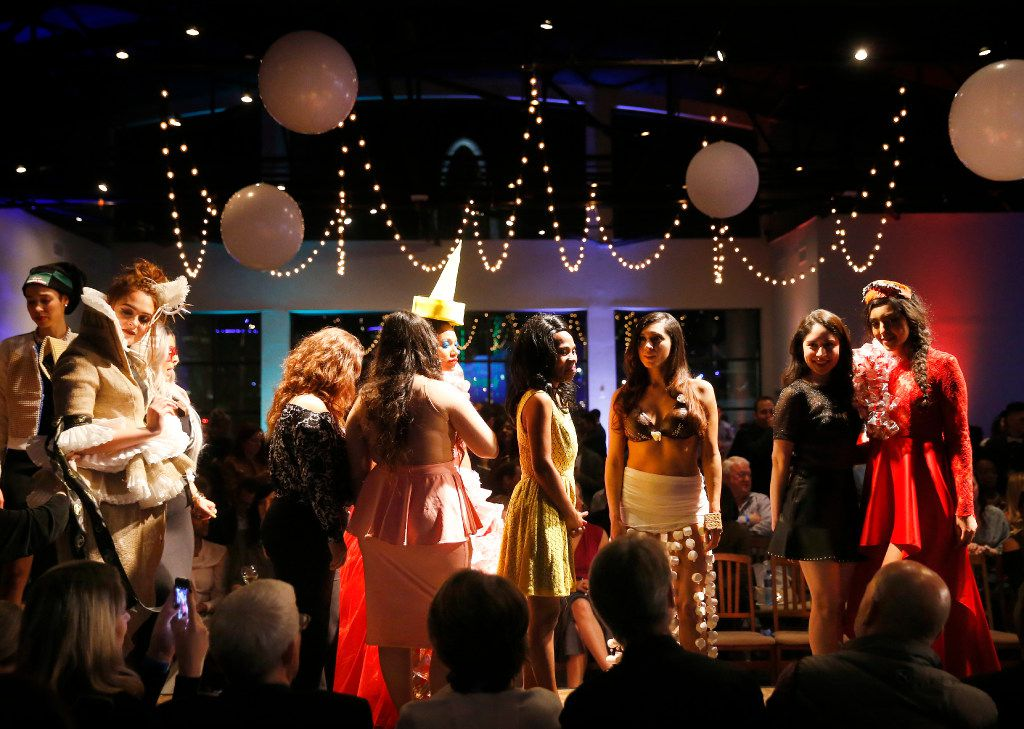 Models and designers pose for photos on the catwalk following their Food in Fashion show at 3015 in the Trinity Groves.
