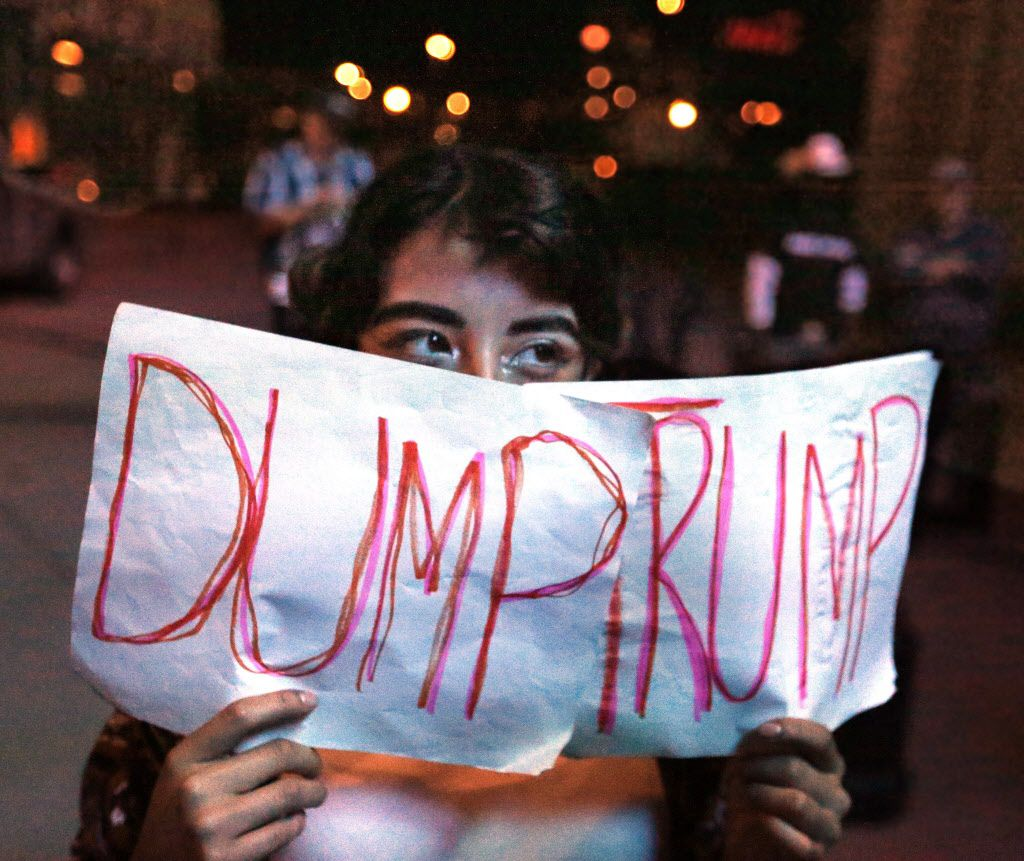 Jennifer Quinones holds a homemade sign during the Next Generation Action Network's  protest against a Trump presidency held outside the American Airlines Center in Dallas on Wednesday, November 9, 2016.